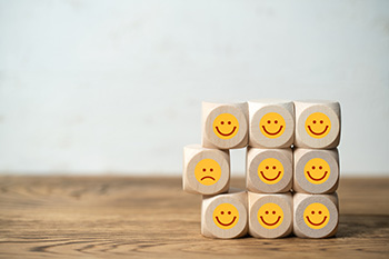 blocks with smiley faces stacked around one block with a frown