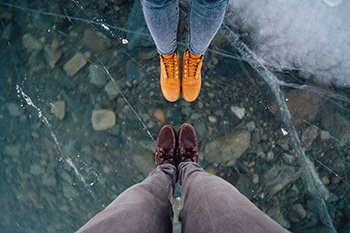 birdseye view of two pairs of feet standing on crystal clear ice