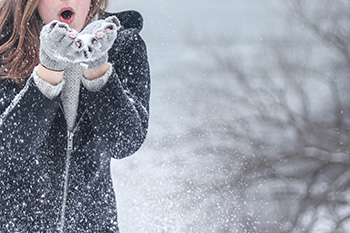 girl blowing snowflakes from her hands